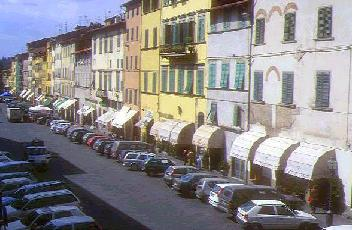 Modern Italian Life With Apartment Blocks, Ground Floor Shops, No Garages  And Lots Of Cars.